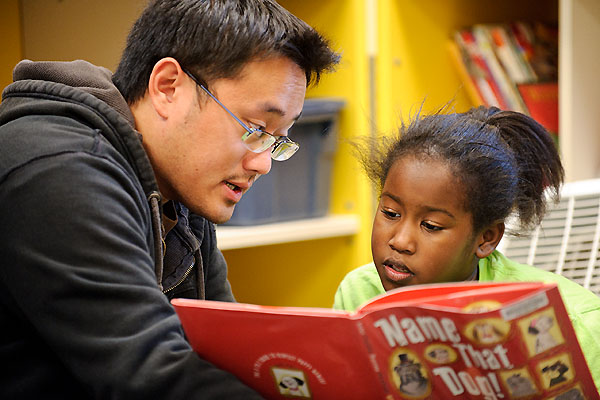 Alum Soon Vue helps Desina Simmons read a book during the Allied Drive Literacy Time program.