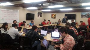 A square set up of tables with students sitting around it with their laptops out.
