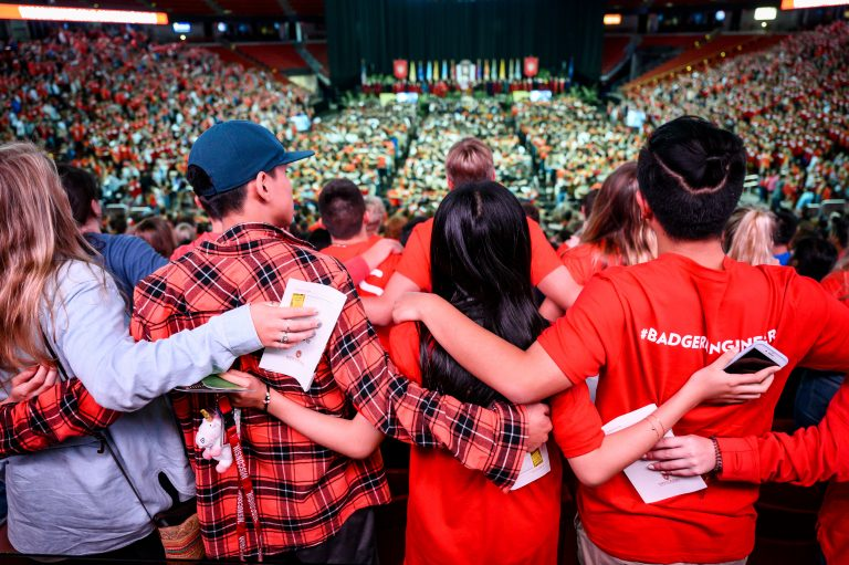 "Incoming first-year and transfer students lock arms and sing ""Varsity"" during the Chancellor's Convocation for New Students, a Wisconsin Welcome event held at the Kohl Center at the University of Wisconsin-Madison on Sept. 3, 2019."